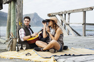 Young couple picnicing on old pier, Cape Town, Western Cape, South Africa - CUF36926
