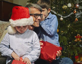 Boy whispering to father whilst brother opens christmas gift - CUF36932