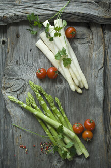 Green and white asparagus, parsley, tomatoes and mixed peppercorns on wood - ASF06190