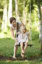 Mid adult mother pushing toddler daughter on garden swing - CUF36974