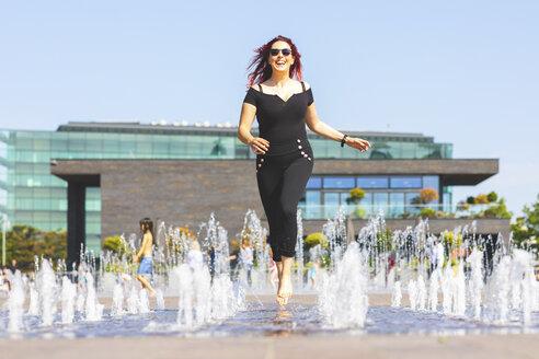 Young woman having fun running through a fountain - WPEF00488