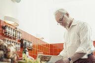 Senior man cooking in kitchen - CUF37016