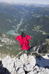 Mature man BASE jumping from mountain, Alleghe, Dolomites, Italy - CUF37061