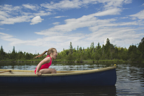 Excited girl sitting in canoe on Indian river, Ontario, Canada - CUF37073