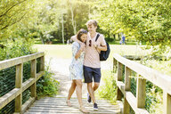 Couple walking over wooden bridge in the park - CUF37085