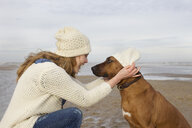 Portrait of mid adult woman and dog on beach, Bloemendaal aan Zee, Netherlands - CUF37124