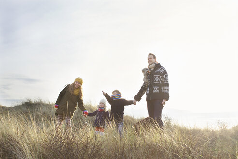 Mid adult couple standing in sand dunes with their son, daughter and dog - CUF37127