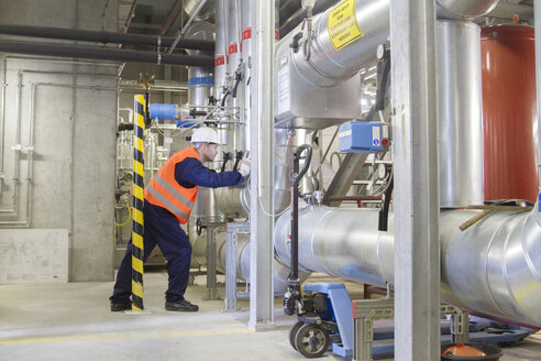 Technician leaning forward during check in power station - CUF37184