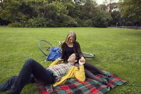 Young couple holding hands on picnic blanket in park - CUF37325