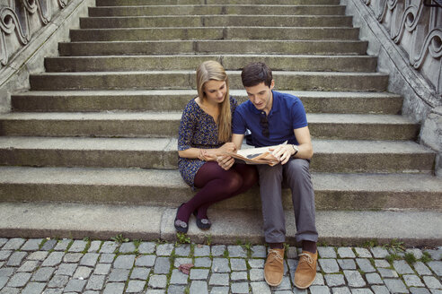 Young couple sitting on old street stairway reading newspaper - CUF37328