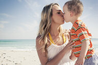 Mid adult mother kissing young son on beach, Cape Town, Western Cape, South Africa - CUF37343