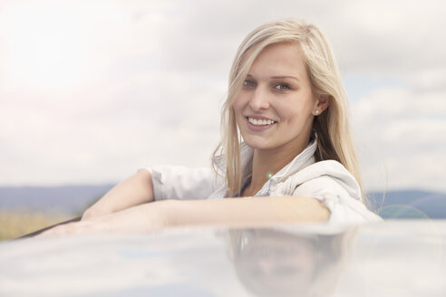 Young woman smiling beside car - CUF37364