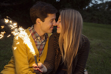 Young couple nose to nose in park holding sparkling firework - CUF37382