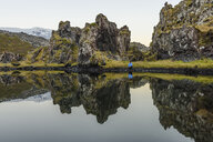 Male hiker crouching by lake and rock formations, Snaefellsnes peninsula, Djupalonssandur, Iceland - CUF37439