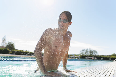 Mid adult man getting out of swimming pool, Sardinia, Italy - CUF37445