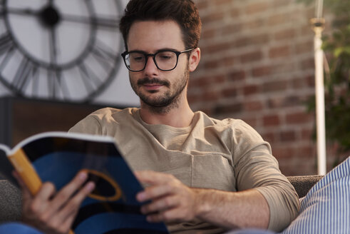 Portrait of man sitting on couch at home reading a book - ABIF00652