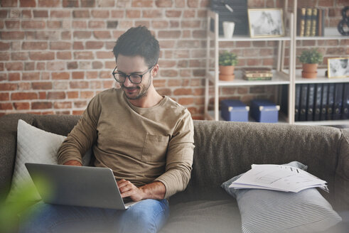 Man sitting on couch at home using laptop - ABIF00658