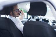 Businessman sitting in car talking on the phone - ABIF00667
