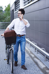 Businessman on the phone pushing his bicycle - ABIF00670