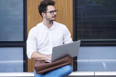 Businessman using laptop outdoors - ABIF00673