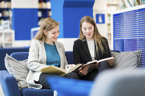 Two teenage girls sitting on couch in a public library reading books - WPEF00505