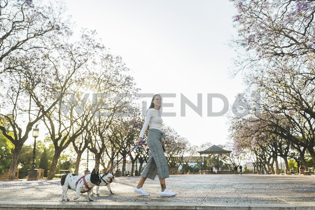 Spain, Andalusia, Jerez de la Frontera, Woman walking with two dogs on square - KIJF01969