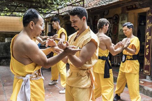 Vietnam, Hanoi, men exercising kung fu, european man learning kung fu - WPEF00521