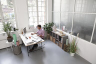 Man working at desk in a loft office - FKF02946