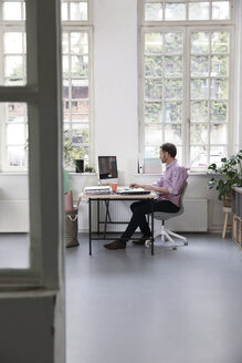 Man working at desk in a loft office - FKF02949