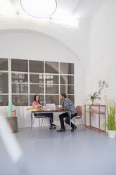 Colleagues sitting at table in an architect's loft office - FKF02985