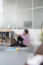 Casual man with plans and laptop sitting on the floor in a loft office - FKF02988