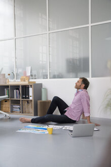 Casual man with plans and laptop sitting on the floor in a loft office - FKF02991