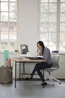 Woman working at desk in a loft office - FKF03009