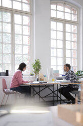 Colleagues working at desk in a loft office - FKF03015