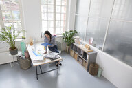 Woman working at desk in a loft office - FKF03021