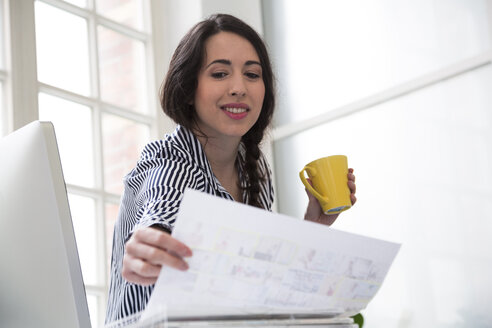 Smiling woman with cup of coffee looking at paper in office - FKF03024