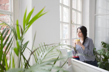 Smiling woman with cup of coffee looking out of window in office - FKF03027