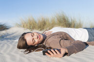 Mid adult woman lying in sand listening to music on earphones, Sardinia, Italy - CUF37466