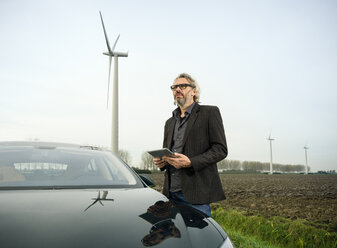 Man by car with wind turbine in background - CUF37484