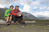 Mature hiking couple sitting with drinks flask and map, Breidvik, Borgafjordur East, East Iceland - CUF37505
