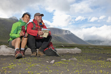 Mature hiking couple sitting with drinks flask and map, Breidvik, Borgafjordur East, East Iceland - CUF37505