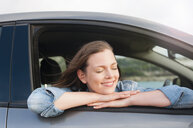 Woman leaning out of car window, Sardinia, Italy - CUF37508