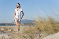 Mid adult woman walking on beach, low angle view - CUF37532