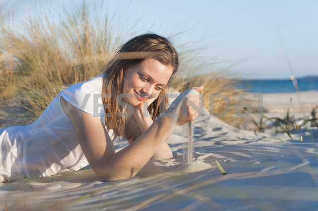 Mid adult woman playing with sand on beach - CUF37535