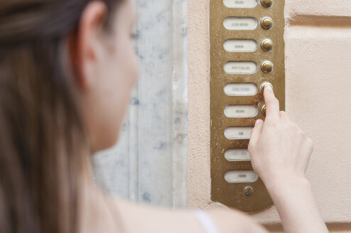 Over shoulder view of mid adult woman pressing apartment doorbell, Sardinia, Italy - CUF37556