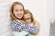 Two sisters holding hugging next to white wall - CUF37601