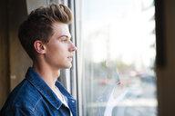 Young man gazing through cafe window - CUF37622