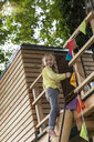 Girl coming down from tree house - CUF37625