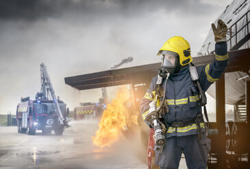 Portrait of fireman in front of simulated fire at airport training facility - CUF37634