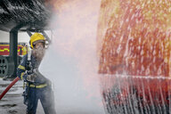 Fireman spraying water on simulated aircraft fire at training facility - CUF37640
